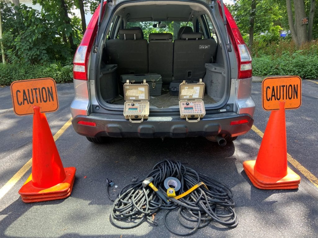 A picture showing the SRPEDD field work car with traffic counting equipment displayed around it including cones, tubes, a hammer, a measuring tape, counters and nails.