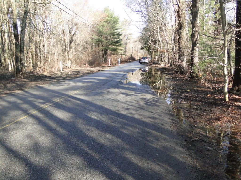 picture showing a flooded roadway with poor pavement conditions