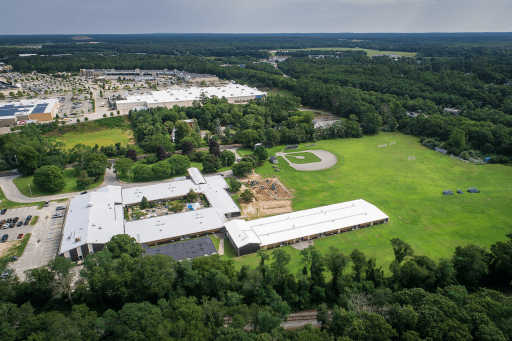 Drone photo looking northeast at the John Decas School in Wareham. There is a shopping plaza visible in the distance.