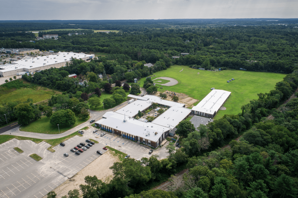 Drone photo looking east at the John Decas School in Wareham. There is a shopping plaza visible in the distance.