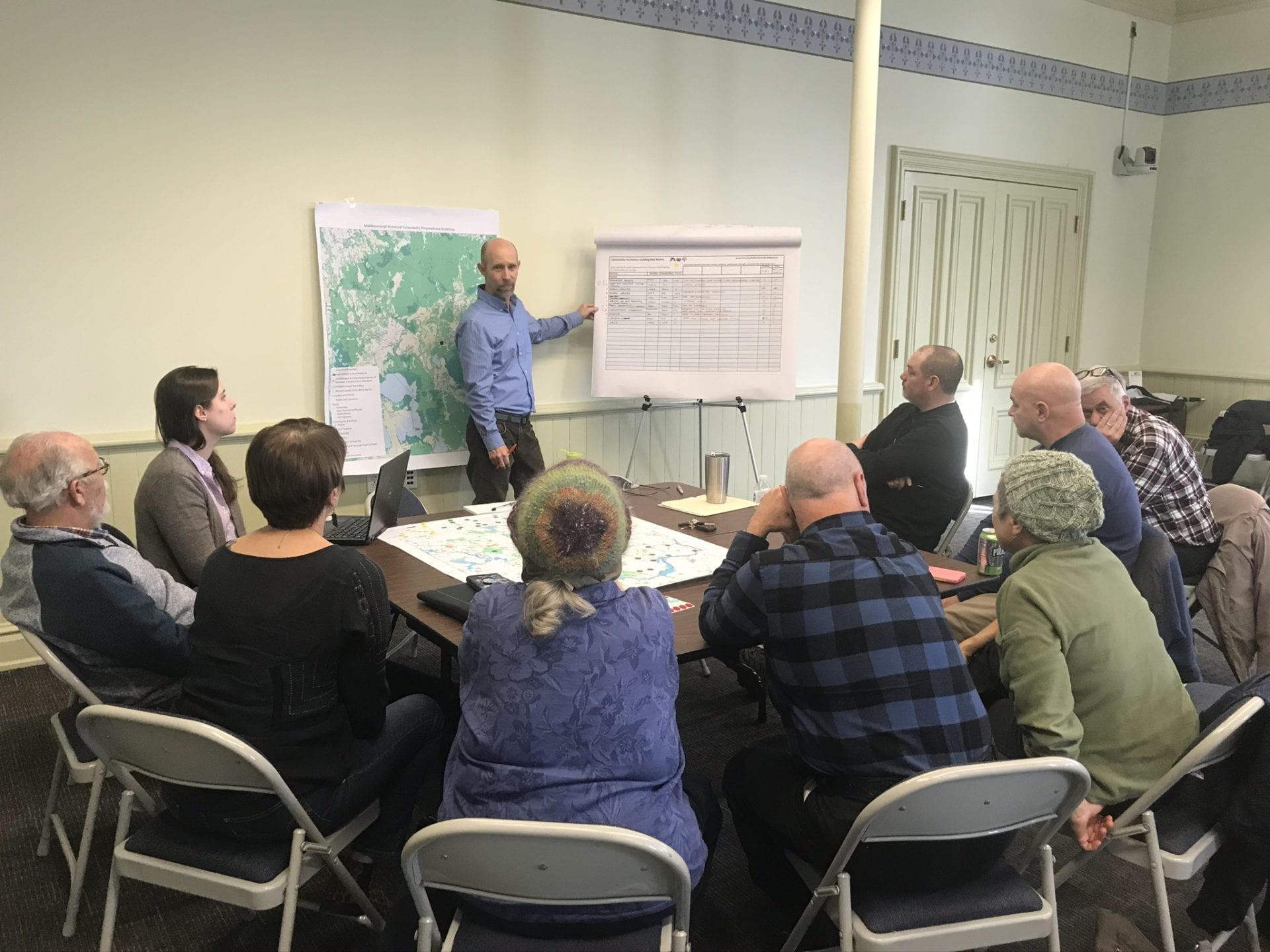 A group of 8 community members and staff from Middleboro MA work with two facilitators to locate climate change related points of concern on a map and describe the issue in a matrix as part of the Municipal Vulnerability Preparedness (MVP) Planning Process